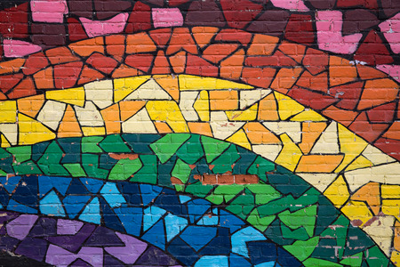 signifies: MONTREAL CANADA AUGUST 20 2014: Street art and graffiti. This rainbow mosaic is painted on a brick wall in the gay quarter of Montreal and signifies gay pride.
