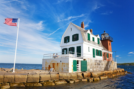 The Rockland Breakwater Lighthouse on a summer afternoon, with US flag flying. Rockland, Maine, USA Stock Photo
