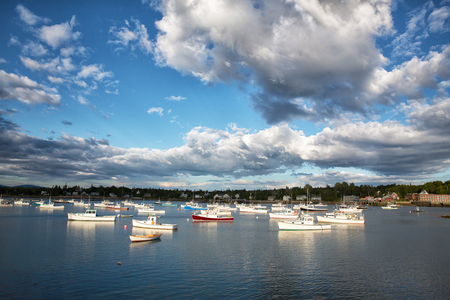cloud formations: Dramatic cloud formations over small fishing and lobster boats in Southwest Harbor, Mount Desert Island, Maine USA Stock Photo
