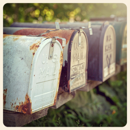 american media: Rusty US mailboxes in the afternoon sun. Instagrm style processing. Filtered to look like an aged instant photo. Stock Photo