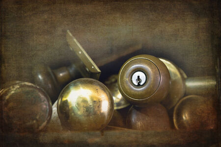 door knobs: Old brass door knobs discarded on a shelf in a workshop. Textured and filtered to look like an old faded photograph.