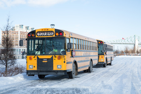 yellow schoolbus: MONTREAL, CANADA - 16 JAN: School buses parked up in the snow and ice wait to collect school children. Montreal, Canada, on 16th January 2015