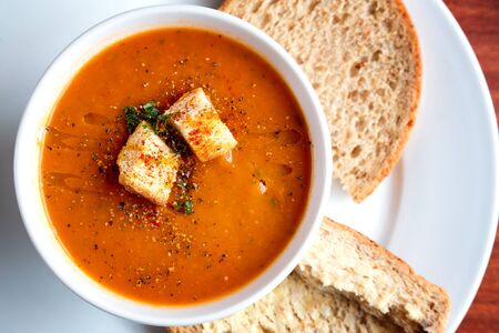 soup bowl: A bowl of fresh tomato soup in white ceramic bowl, garnished with herbs, croutons, seasoning and a drizzle of olive oil, and served with crusty wholemeal bread.