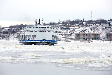 levis: Passenger Ferry crosses the frozen St Lawrence river from Levis to Quebec City, Canada. Identifying marks removed. Stock Photo