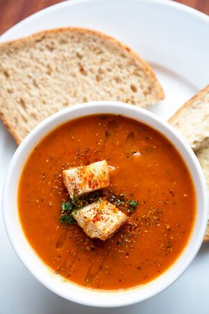 drizzle: A bowl of fresh tomato soup in white ceramic bowl, garnished with herbs, croutons, seasoning and a drizzle of olive oil, and served with crusty wholemeal bread.