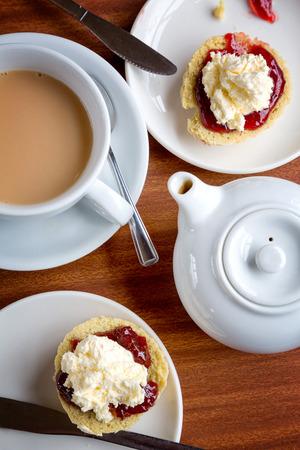 따뜻한 차 한잔과 함께 응고 크림과 잼과 스콘의 전통적인 영어 애프터눈 티. 스톡 콘텐츠