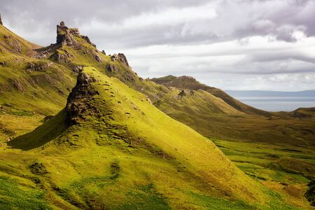 highland: Scenic view of Quiraing mountains, a popular destination for hikers, with dramatic sky in the Isle of Skye, Scottish highlands, United Kingdom