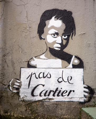 exploited: PARIS, FRANCE - MARCH 3RD: Graffiti figure of a poor girl being exploited by the International Company of Cartier. The Slogan Pas De Cartier translates as No to Cartier. On March 3rd 2015
