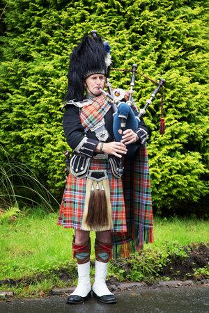 gaita: INVERARAY, Escocia - 28 de julio de 2015: gaitero escocés, en el traje nacional completa, toca la gaita. Editorial