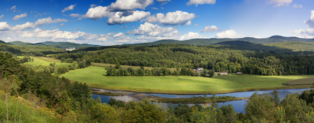 A panorama of the lush green countryside of the State of Vermont in the summertime. A river meanders through the pastures.