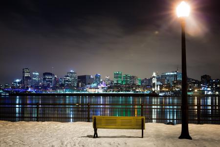 Een winterse nacht in Montreal. Bankje in het park en de straat licht met de rivier en het centrum van Montreal St Lawrence op de achtergrond. Stockfoto