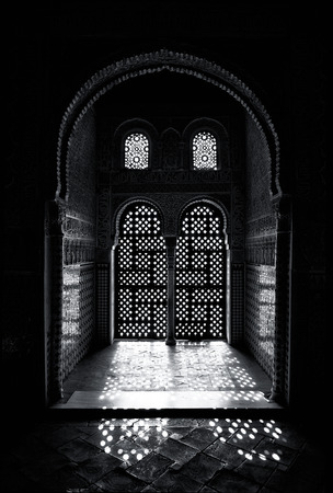 islam: Arabesque style ornate window detail, with sunlight shining through. Black and white. Stock Photo
