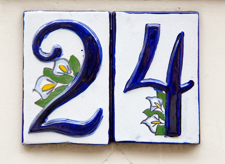 delftware: House number in Amsterdam, made in the traditional delftware style, with blue and white tin glaze, decorated with calla lilies.