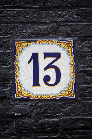 delftware: Decorative delftware tile with the number 13, on a black painted wall in Amsterdam,