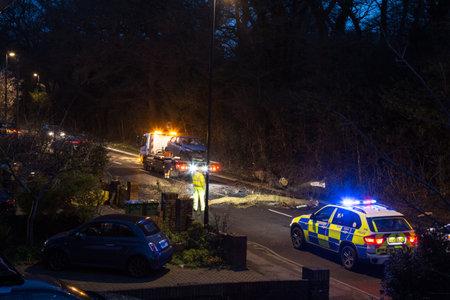 emergencia: Southampton, Inglaterra - 8 de febrero de 2015: Los servicios de emergencia se recuperan vehículo, que ha sido golpeado por un árbol que cayó durante la tormenta Imogen, en el límite de lo común, Southampton, Reino Unido.