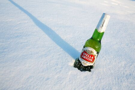 pilsner: MONTREAL, CANADA -21 January 2015: A bottle of Stella Artois beer cools in the winter snow. A European pilsner beer, very popular in Canada. Montreal, january 2015