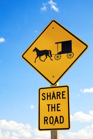 amish buggy: A road sign warning drivers to share the road with the local Amish horse and buggies. Stock Photo