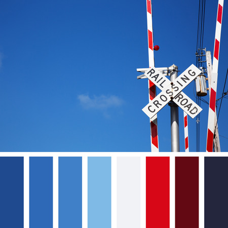 complimentary: Railroad crossing sign against blue sky background. In a colour palette with complimentary colour swatches.