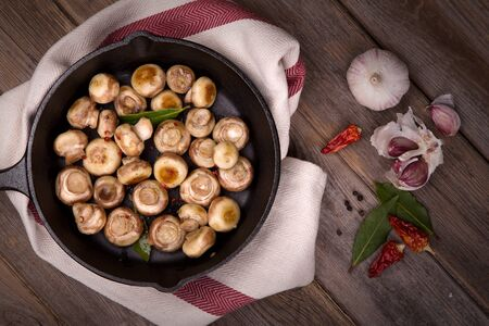 tea towel: Button mushrooms with garlic, fried in a cast iron skillet, resting on a tea towel over an old wood background. Stock Photo