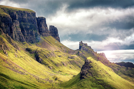 Scenic view of Quiraing mountains, with dramatic sky in the Isle of Skye, Scottish highlands, United Kingdom. Cinematic style processing with lens flare. Stock Photo