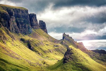 Vista panorámica de las montañas de Quiraing, con el cielo dramático en la isla de Skye, tierras altas de Escocia, Reino Unido. procesamiento de estilo cinematográfico con reflejo en la lente. Foto de archivo