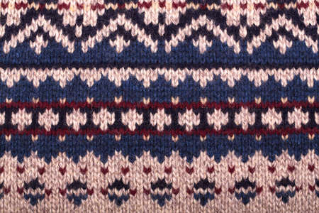 purl: Hand knitted background with traditional geometric pattern in purl stitch. Natural wool in beige, navy blue and burgundy colour scheme. Stock Photo