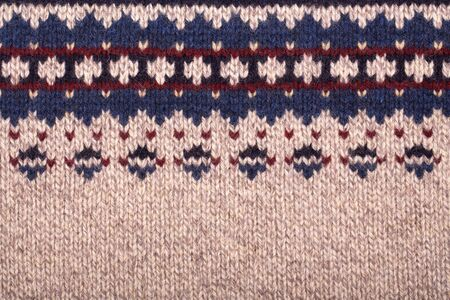 burgundy colour: Hand knitted background with traditional geometric pattern in purl stitch. Natural wool in beige, navy blue and burgundy colour scheme with space for text. Stock Photo