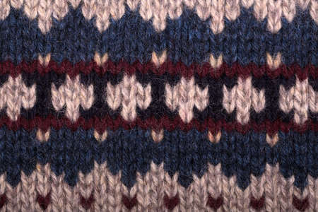 burgundy colour: Hand knitted background with traditional geometric pattern in purl stitch. Natural wool in beige, navy blue and burgundy colour scheme. Stock Photo