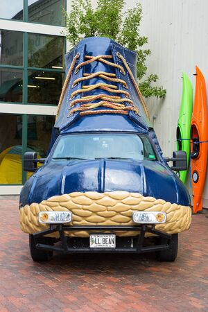 freeport: FREEPORT, MAINE, USA-AUG 31st, 2014: L.L. Bean is retail company founded in 1912 by Leon Leonwood Bean. A replica of its famous boot has been coverted to a promotional vehicle and stands outside the flagship store.