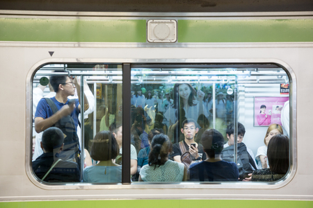 TOKYO, JAPAN - June 19 2016: Busy commuter  train at Shinjuko station. This is the busiest train station in the world and 3.4 million people pass through it each day. In Tokyo, Japan 2016
