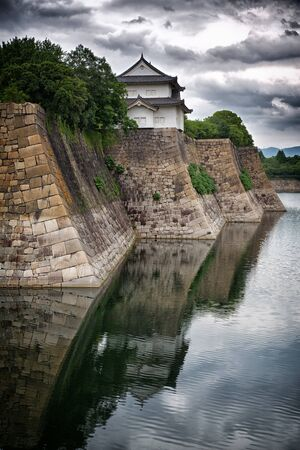Osaka Castle walls and moat. Dramatic skies with mirrored reflection.