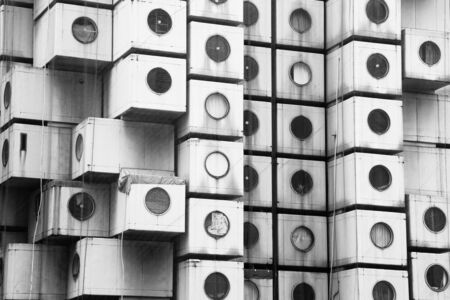 postwar: TOKYO, JAPAN - 22 JUNE 2016: The iconic Nakagin Capsule Tower in Shimbashi,Tokyo. Built in 1972  designed by Kisho Kurosawa and a rare surviving example of Japanese Metabolism style. Black and white. Editorial