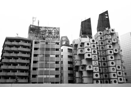 surviving: TOKYO, JAPAN - 22 JUNE 2016: The iconic Nakagin Capsule Tower in Shimbashi,Tokyo. Built in 1972  designed by Kisho Kurosawa and a rare surviving example of Japanese Metabolism style. Black and white. Editorial