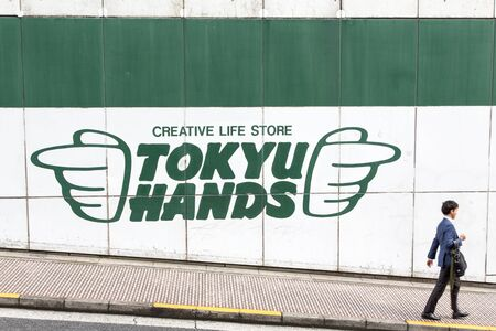 passerby: TOKYO, JAPAN - 21 JUNE 2016: A direction sign for the iconic Tokyu Hands store  points to a passerby, in Shibuya, Tokyo. Editorial