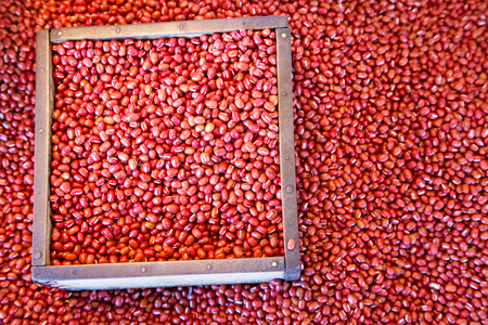 Azuki, or aduki, beans for sale at a market in Japan. The beans are native to northeast Asia and are a staple part of the Asian diet. Selective focus on beans in box with space for text.