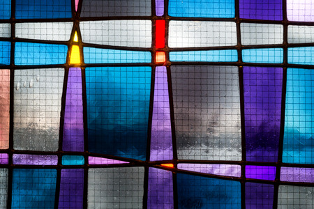 Abstract stained glass detail in tones of blue, turquoise and purple.