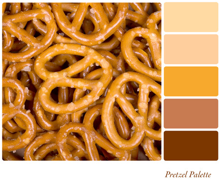 A background of golden pretzels, in a colour palette with complimentary colour swatches. Stock Photo