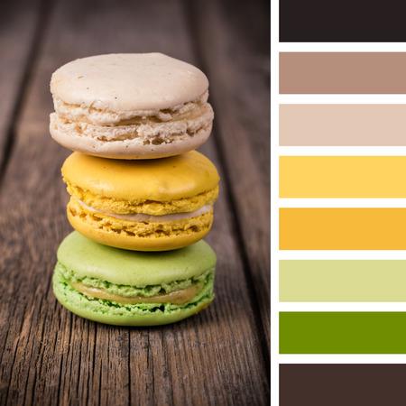 paleta de pintor: macarrones franceses en un viejo fondo de madera. En una paleta de colores con muestras de color de regalo.