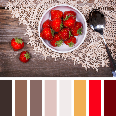 Fresh strawberries in a white ceramic bowl, on old wood background with lace tablecloth. In a colour palette with complimentary colour swatches.