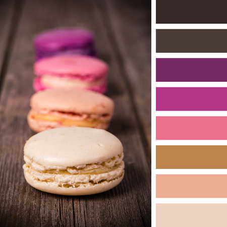 French macaroons on an old wood background. In a colour palette with complimentary colour swatches.