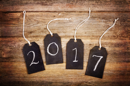 resemble: 2017 written on chalkboard gift tags, over old wood background. Textured to resemble an aged photo.