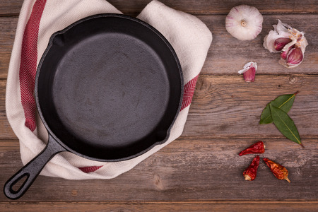 Empty cast iron skillet with herbs and spices, resting on a tea towel  over an old wood background. Retro style processing and space for your text.