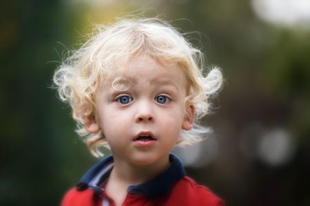 小さな男の子は、外で遊ぶ。ブロンドの髪と青い目の 2 歳の幼児の肖像画。