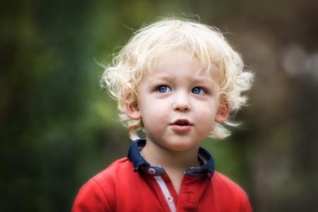 niños rubios: Pequeño niño jugando fuera. Retrato de niño de 2 años con el pelo rubio y ojos azules.