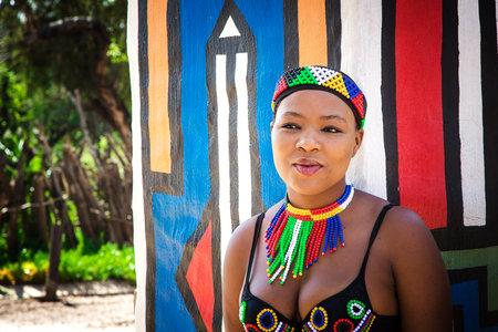 Lesedi Cultural Village, SUDÁFRICA - 4 de noviembre 2016: Mujer Zulu joven en traje de trabajo del grano tradicional colorido.