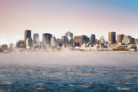 Steam rising from the frozen St Lawrence river at sunrise, with the Downtown district of Old montreal in the background. Archivio Fotografico