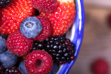 closeup view: Overhead closeup view of summer fruits in a blue-rimmed ceramic bowl, with blueberries, strawberries, raspberries and blackberries.