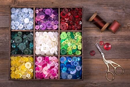 sewing box: A box of colourful buttons, sorted into colour groups, in an old wood box. Spools of thread, a needle and embroidery scissors are placed to one side. Needlecraft and scrapbooking theme.