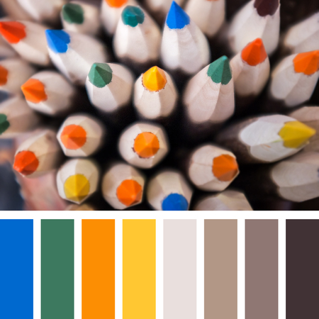 Coloured pencils top view with selective focus on central pencil. In a colour palette with complimentary colour swatches. Stock Photo