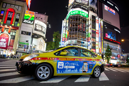 Tokyo, Japan - 19 June 2016: Toyota Prius, energy efficient taxicab in Shinjuku, Tokyo. Night scene  on busy intersection in the commercial shopping district. Editorial